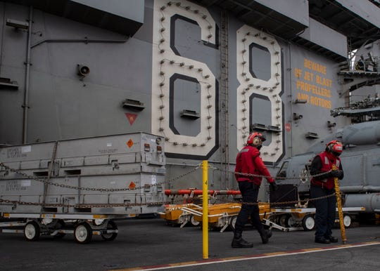Sailors transport ordnance during an ammo delivery on the flight deck of the aircraft carrier USS Nimitz. The Nimitz Carrier Strike Group deployed Monday.