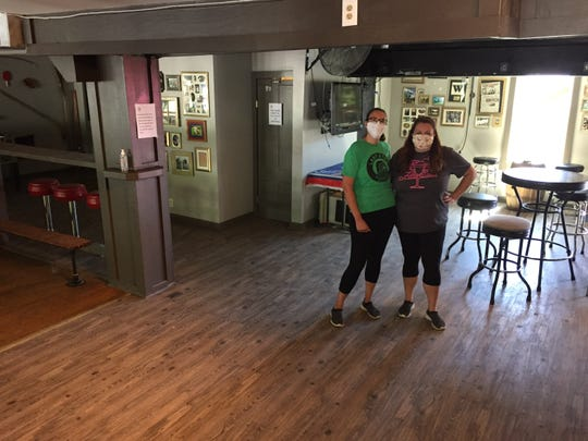 Shalya Ruland (right), owner of the Last Stop Sports Bar, and her sister, bartender Kaitlyn Ruland, stand in the Winooski bar's socially-distanced interior June 8, 2020.