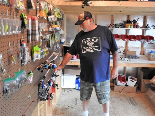 Ken Jennings of Tuck's Bait and Tackle sets out some new fishing poles at the business near Wills Creek. They also offer fishing and hunting license and hope to expand to hunting related items next year.
