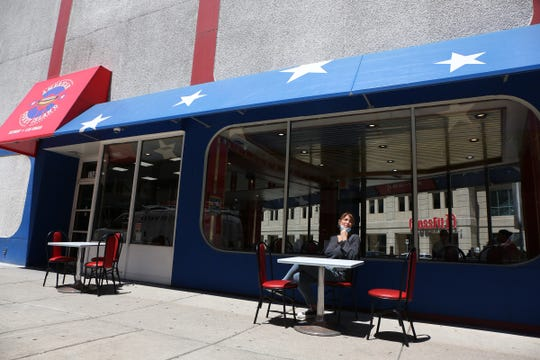 Grace Keros, owner of American Coney Island sits in front of her restaurant on Monday, June 8, 2020. American Coney Island opens up at 50 percent capacity for the first time since the coronavirus started.