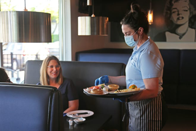 Server Lea Fernandez of West Bloomfield delivers food to Ilene Bischer of Macomb Township at Stage Deli in West Bloomfield on June 8, 2020, the day metro Detroit restaurants could offer dine-in service again for the first time since the COVID-19 crisis began.