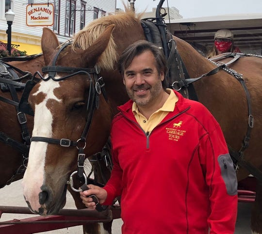 Brad Chambers, owner of Mackinac Island Carriage Tours, is pictured here last Friday on Main Street. He's eager to welcome visitors after a delayed opening.