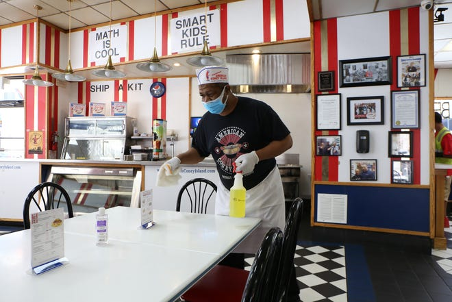 Calvin Rakestraw, 53, of Detroit, cleans off a table at the American Coney Island on Monday, June 8, 2020.