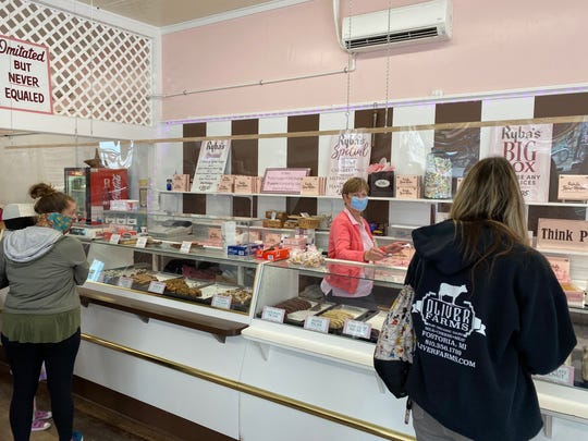 Pamela Deckert serves patrons from behind the counter at Ryba's Fudge on Mackinac Island on Sunday, June 7, 2020. The business is one of many on island that has installed barriers to protect workers and customers during the pandemic. All wear face masks this summer.