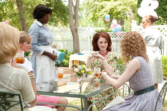 "Viola Davis, standing at left, stars in ""The Help"" with Bryce Dallas Howard, center, Ahna O'Reilly, left, and Emma Stone, right."