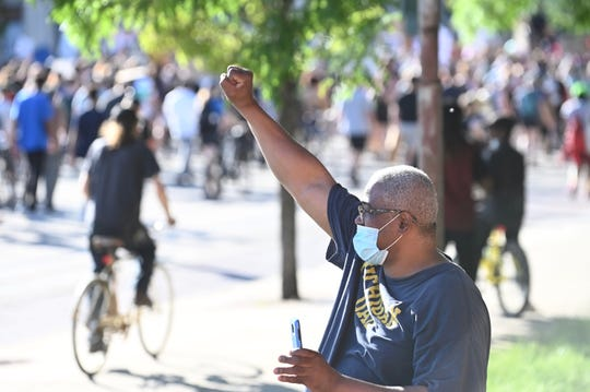 Gregory H. Groves raises his fist in unity as he watches protesters march along Woodward Avenue on Monday, June 8, 2020.