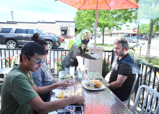 Server Megan Daniels brings out lunch for David Gennero, Isabella Gennero and Alexander Gennero of Royal Oak in the outside dining area of Zeoli's in Clawson.