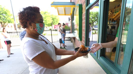 Tracey Collins, of Detroit, gets a waffle bowl with carmel at the walk up window at Wally's Frozen Custard & Coffee Station in St. Clair Shores, June 7, 2020.