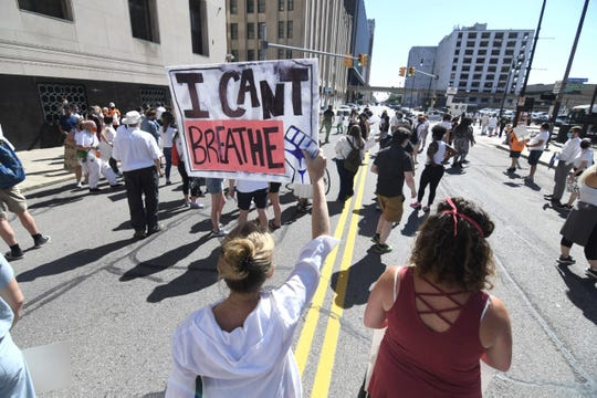 People display signs during a protest march along Lafayette Boulevard in Detroit on Monday, June 8, 2020.
