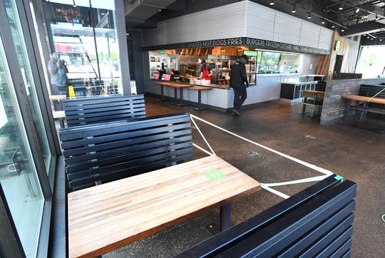Keeping 6-foot social distancing in mind, the Shake Shack in Troy tapes off every other table in its indoor dining area.