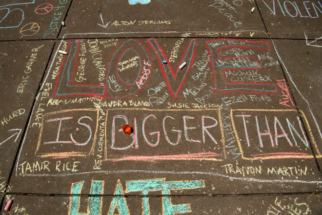 Chalk messages dot the sidewalk at the children's protest rally with chalk at Ford Center in Evansville Saturday afternoon, June 6, 2020.