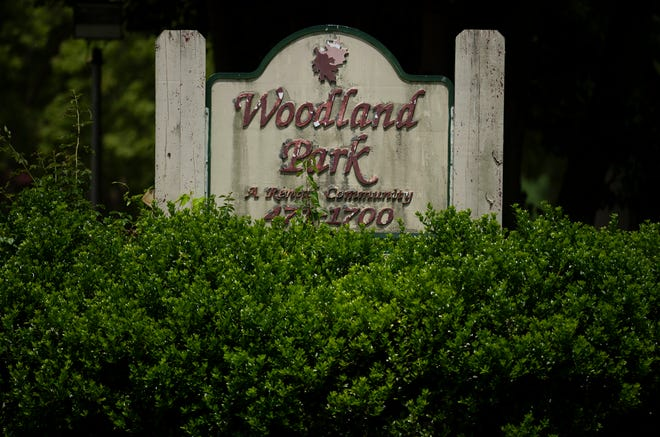 In this 2020 file photo, bushes had grown tall enough to nearly obscure the sign at Woodland Park Apartments on Evansville's South Side.