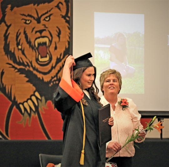 Megan Helle flips her tassel with Principal Sonia Herman watching during Gibsonburg High School's  graduation ceremony on Sunday.