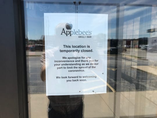 A sign posted to the front doors of the Applebee's at 900 Hansen Road, in Ashwaubenon, notes it is temporarily closed due to coronavirus. Applebee's officials say the location will resume carryout service Thursday, June 11, and dine-in on Wednesday, June 17.