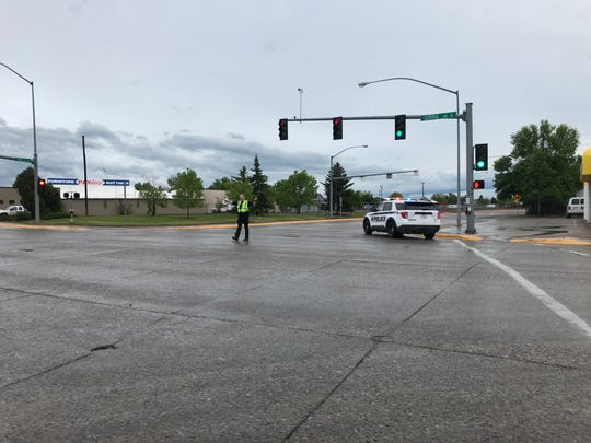 A police officer directs traffic at Central Avenue West and 3rd Street Southwest Sunday evening after a thunderstorm caused the railroad lights to malfunction. Minor street flooding also was reported.