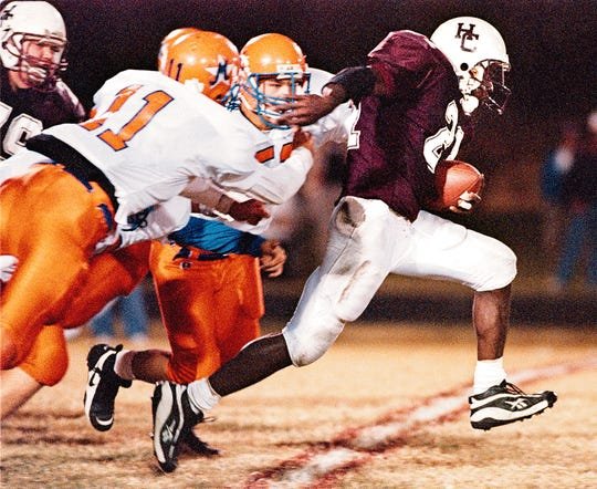 Henderson County's Jonathan Jackson (21) breaks away from would-be Marshall County tacklers as he sprints down field to gain several yards for the Colonels during the 1998 game at Colonel Stadium.