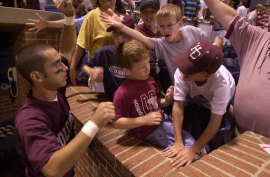 Fans slap the hand of Henderson County player Andy Capps after the Colonels beat Nicholas County 5-2 in the 2000 state semifinals at Cliff Hagan Stadium in Lexington.
