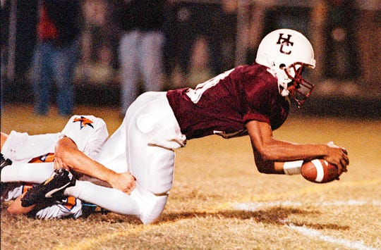 Henderson County quarterback Schile Cosby dives into the end zone as he scores a touchdown for Henderson County in their 1998 game against Marshall County.
