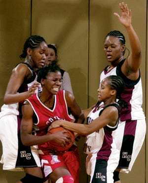 Henderson County's Sierra Gilbert (15) battles for the ball with Christian County's Arnika Brown (32) as Henderson's Whitney Waddell (44), left, and Christal Floyd (54) back her up during their 2004 game at Colonel Gym.