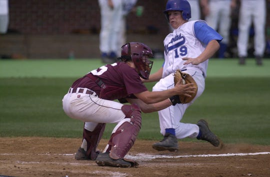 Henderson County catcher Joel Booker (15) tags out Nicholas County's Josh Fryman (19) at home plate during the 2000 state semifinal game at Cliff Hagan Stadium in Lexington.