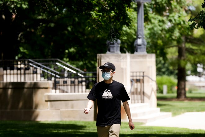 A pedestrian wears a mask as they walk past the Purdue Memorial Union, Monday, June 8, 2020 in West Lafayette.