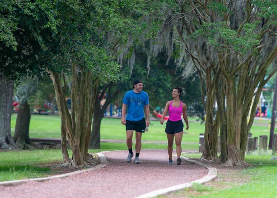 Chris Seither and Jamie Villagomez walking in Girard Park as Tropical Storm Cristobal failed to bring severe weather to Acadiana. Monday, June 8, 2020.