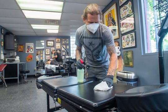 """Triple A Tattoo & Piercing Owner Coby Cox cleaning surfaces. Monday, June 8, 2020. Opening up again was """"kind of weird"""" but a welcome sigh of relief.  """"All the customers are just being super helpful, nobody is really upset about the situation,"""" he said. """"It's a good vibe for everyone."""""""