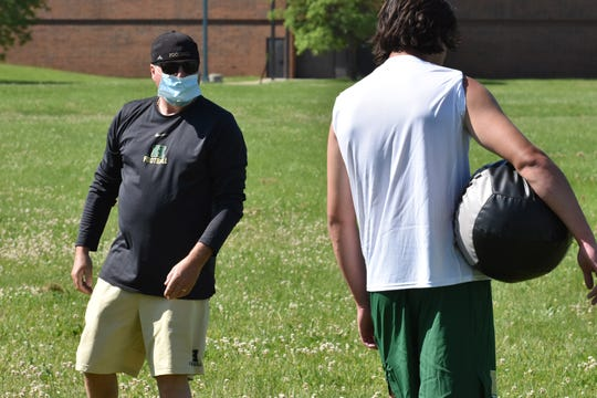 Howell assistant football coach Gary Sutherland wears a mask while leading a workout on Monday, June 8, 2020.