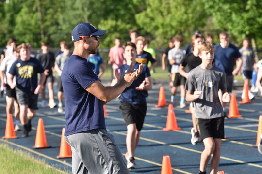 Hartland strength and conditioning coach Mike Cieszkowski puts football players through a workout on Monday, June 8, 2020.