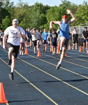 Hartland football players work out on the high school track on Monday, June 8, 2020.