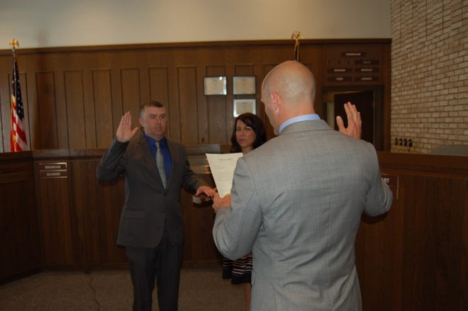 Josh Bradley, left, was sworn in Wednesday as Ontario's newest councilman by Andrew Medwid, law director, while Amy, his wife, held the Bible.