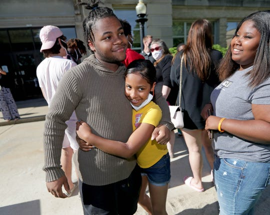 Eric Patrick Lucas, III, 17, gets a hug from Harmonee Goston, 9, whose sister is friends with Eric as Eric's friend, Kayla Mcpike, looks on after a news conference at Shorewood High School on Monday. Lucas discussed being spat on by 64-year-old Stephanie Rapkin a during a Black Lives Matter march in Shorewood on Saturday.