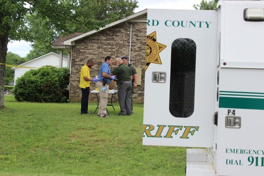 Deputies investigate the shooting scene where a man's body was found in a car Monday morning.