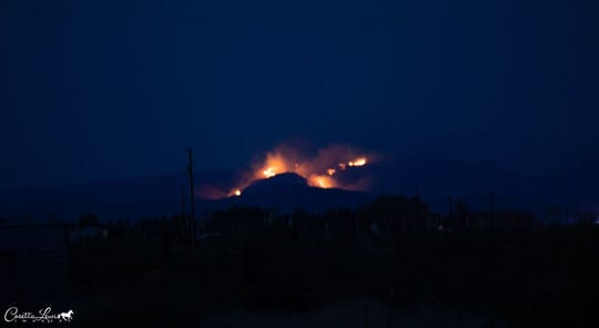 A fire in the Sierra de las Uvas mountain range is seen from the Deming area, about 25 miles away from the fire, on Saturday, June 6, 2020.
