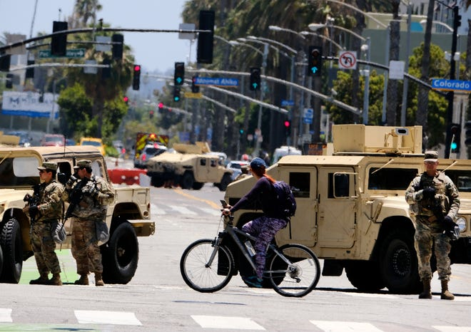A cyclist rides past a road block with National Guard troops along Ocean boulevard in Santa Monica, Calif. on Sunday June 7,2020.  Officials announced Sunday that National Guard troops will be pulled out of California cities where they've been deployed for a week after rampant violence and thievery marred the first days of protests over the death of George Floyd. (AP Photo/Richard Vogel)