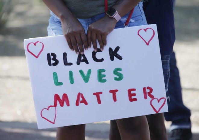 A woman holds a sign before a march against racism and police brutality in Old Town Scottsdale on June 7, 2020.
