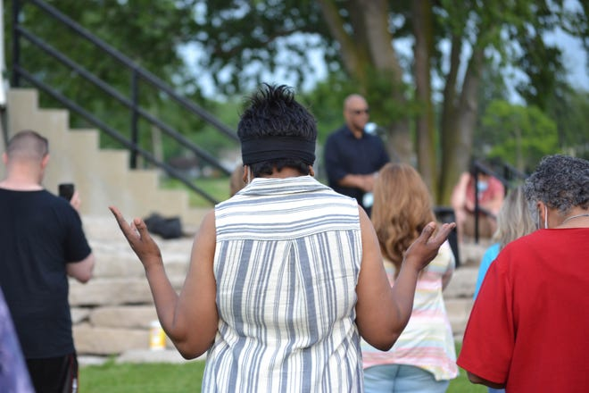 A woman raises her hands and bows her head in worship as a local pastor leads the group in prayer. People of several different faiths and races gathered together to pray for love and unity at the Port Clinton Lighthouse on Thursday night.