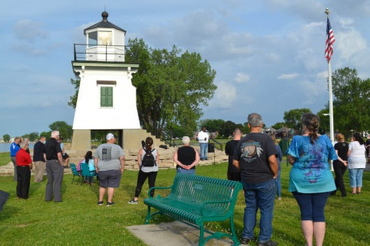 Pastor Anton Jackson of Erie Shores Assembly of God talks to the crowd about the connection between their love and God's love at the Port Clinton Lighthouse on Thursday night.