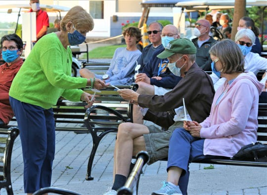 Residents and guests of Lakeside Chautauqua light candles for peace and justice Sunday in a service held in the Steele Memorial Bandstand in Bettinger Park.