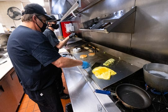 Ocean Breeze cooks John Liangos, left, and Larry Cluesman, prepare food in the restaurant's kitchen Monday, June 8, 2020, in Marysville. Restaurants in Michigan were able to open to dine-in business at 50 percent capacity for the first time since mid-March Monday.