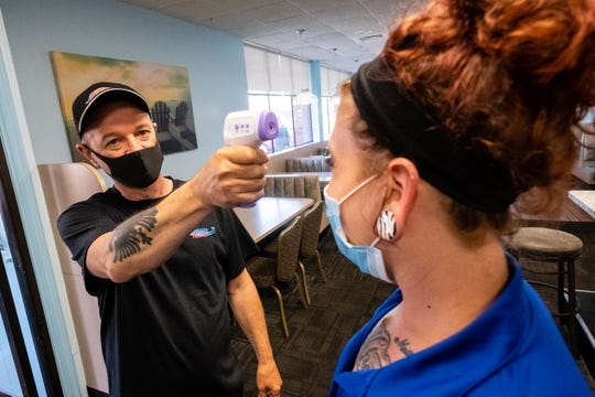 Pete Cubi, owner of Ocean Breeze in Marysville, left, takes Stephanie Dineen's temperature during her shift Monday, June 8, 2020. As they reopen, every person who enters the restaurant will have their temperature checked.