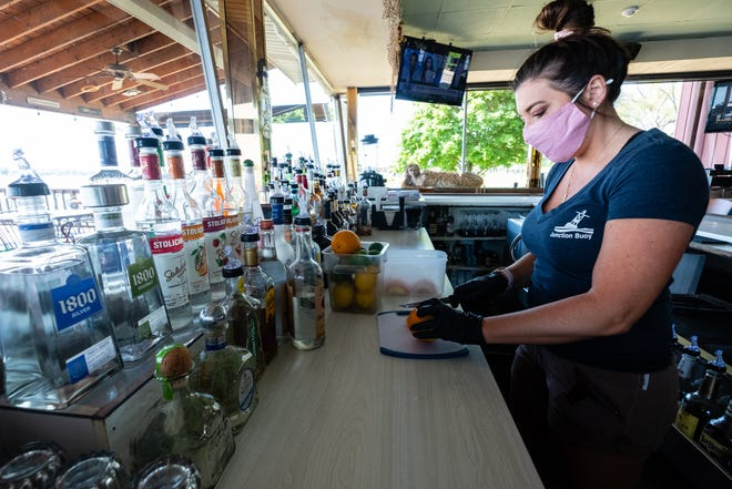 Kelly Long, a manger at Junction Buoy, cuts fruit ahead of their opening Monday, June 8, 2020, in Marysville. Restaurants in Michigan were able to open to dine-in business at 50 percent capacity for the first time since mid-March Monday.