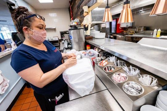 Shari Rupp, head waitress at Ocean Breeze, bags a to-go order Monday, June 8, 2020, in Marysville.