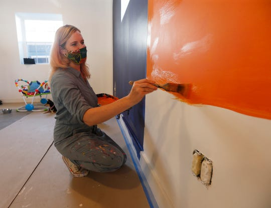 Happy Valley Arcade Bar owner Alyssa Follansbee works on painting the interiors of the bar and arcade in Beacon on June 8, 2020.