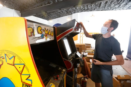 Happy Valley Arcade Bar owner Johnny Coughlin dusts off one of the bar and arcade's arcade games in Beacon on June 8, 2020.
