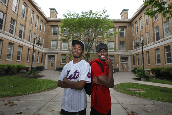Brothers Desire Chiruza, left, and Armand Chiruza, right, pose outside Wilson Magnet High School on Genesee Street in Rochester Wednesday, June 3, 2020. The pair, refugees from the Democratic Republic of Congo by way of Uganda, are graduating from Wilson this month.