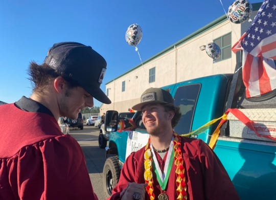 Long-time friends and classmates Tyler Weekley and David Reese exchange congratulatory greetings in front of the Happy Valley Elementary School parking lot before mounting their vehicles to begin the Graduation cruise.