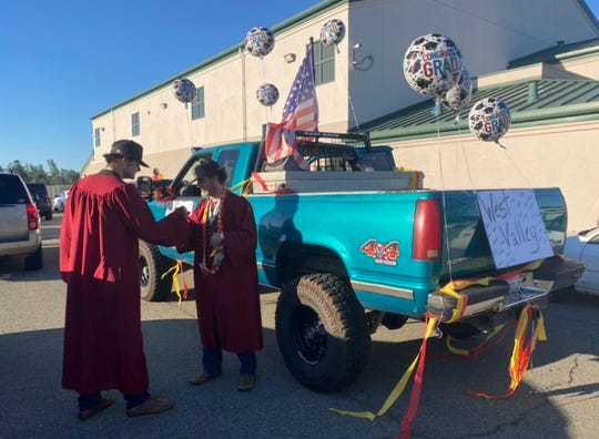 Tyler Weekley and David Reese exchange congratulatory greetings in front of the Happy Valley Elementary School parking lot before mounting their vehicles to begin the Graduation cruise.