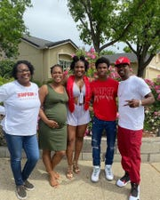 """Ravien Lawson, left center, is joined by her mother Barbara, left, sister Alex Cooper, center, brother Demarreya Lewis-Cooper, right center, and father Lamont """"Disco"""" Cooper, right, in a photo from 2020."""