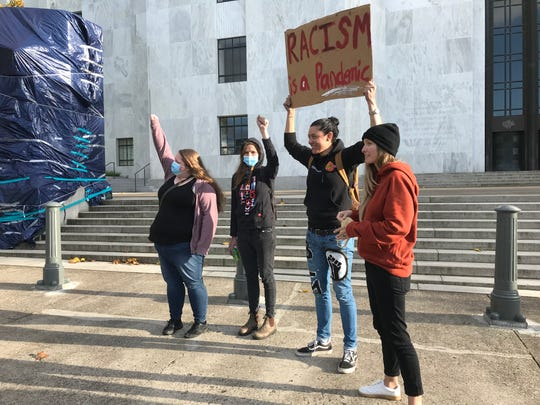 Holding a sign and waving to passing motorists, Kristin Marquardt and her friends were among a small group of demonstrators that maintained a presence at the Oregon State Capitol on Sunday, June 7, 2020, to pay tribute to George Floyd, a black man who was killed by police in Minneapolis.